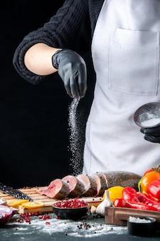 正面図のシェフは、キッチンテーブルの木製のサービングボードのまな板野菜の生の魚のスライスに小麦粉を振りかけました