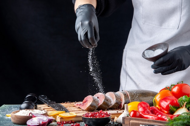 Front view chef sprinkled flour on raw fish slices on cutting board vegetables on wood serving board knife on kitchen table