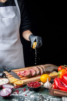 キッチンテーブルのまな板に生の魚のスライスナイフでレモンを絞る正面図のシェフ