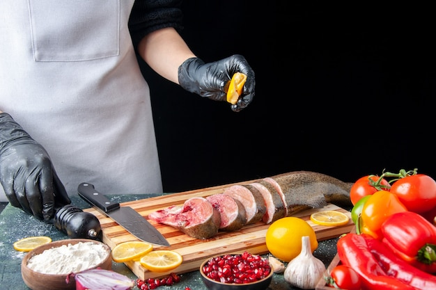 Front view chef squeezing lemon on raw fish slices knife on cutting board vegetables on wood serving board