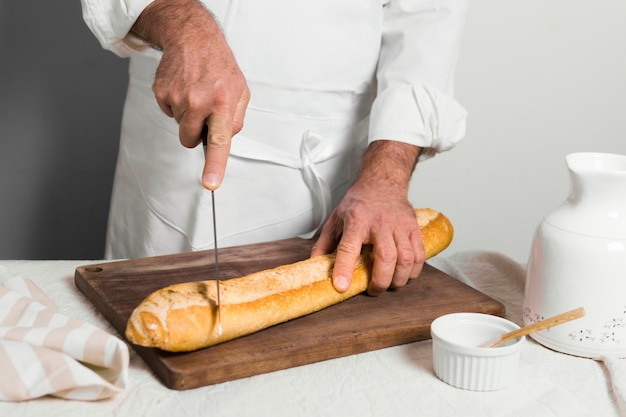 Front view chef wearing white clothescutting a baguette