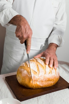 Front view chef wearing white clothes cutting a bread