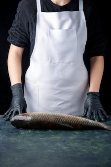 Chef di vista frontale in grembiule bianco pesce fresco sul tavolo