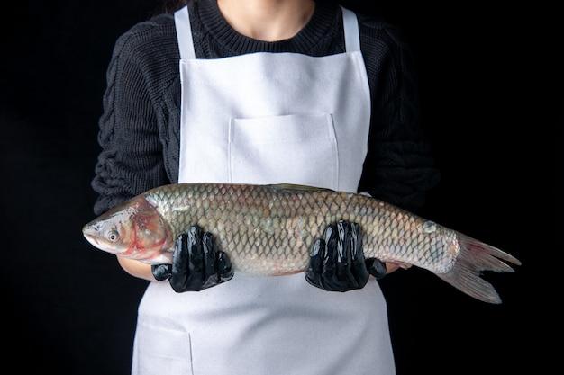 Chef vista frontale con guanti neri che tengono pesce fresco su superficie scura