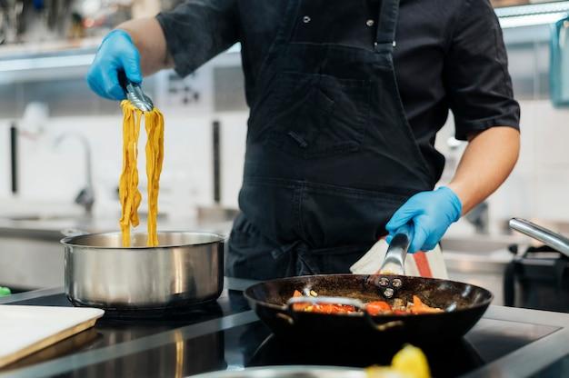 Vista frontale dello chef con guanti che cucinano la pasta in cucina