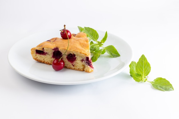 Front view of cherry cake slice inside white plate with green tree leaves on the white surface