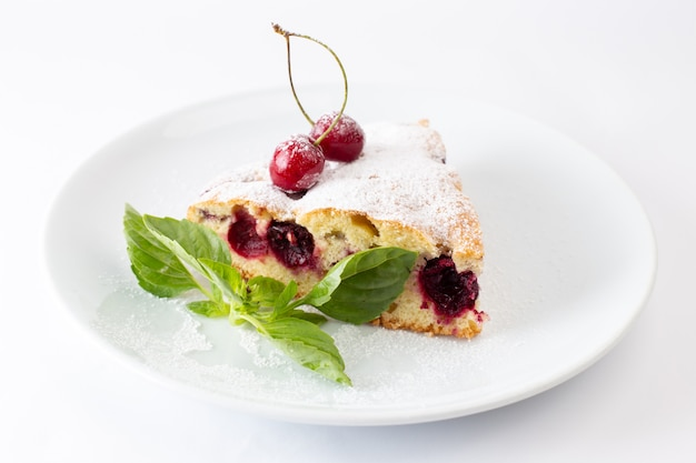 Front view of cherry cake slice inside white plate with sugar powder on the white desk
