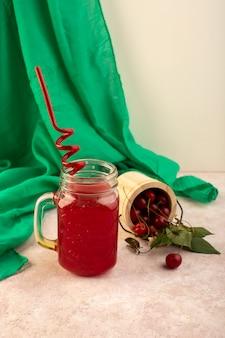 Un rosso cocktail ciliegia vista frontale con paglia all'interno poco può rinfrescare il raffreddamento insieme a ciliegie fresche sul rosa