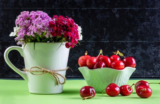 Вид спереди вишня в вазе с букетом разноцветных цветов в чашке