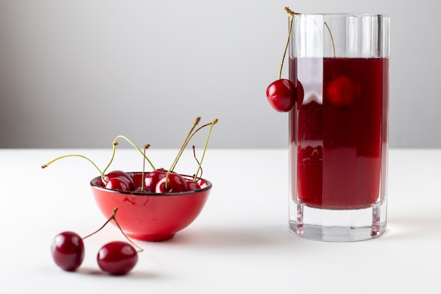 Front view of cherry juice inside long glass with fresh cherries on the white surface