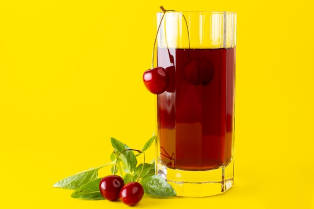 Front view of cherry juice inside long glass on the yellow surface
