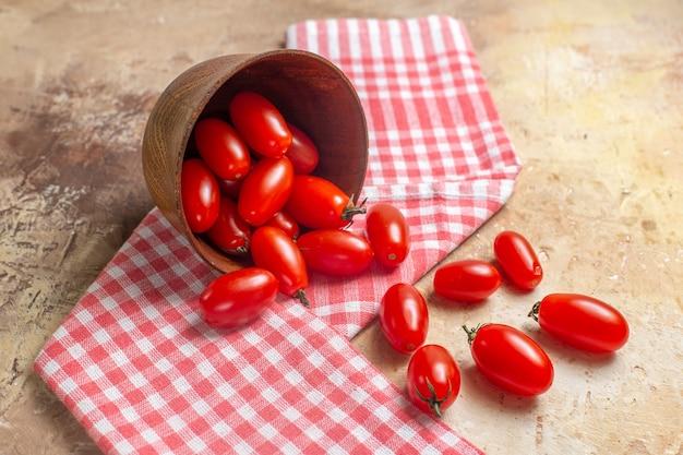 호박색 배경에 주방 수건이 그릇에서 흩어져 있는 전면 뷰 체리 토마토