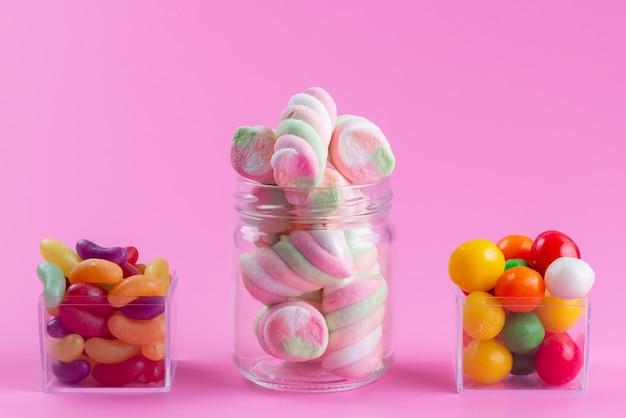 Una vista frontale che mastica marshmallow insieme a marmellate colorate e caramelle su rosa, caramella color dolce