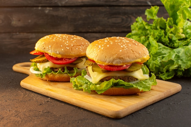 A front view chicken burger with cheese and green salad on the wooden desk and sandwich fast-food meal food