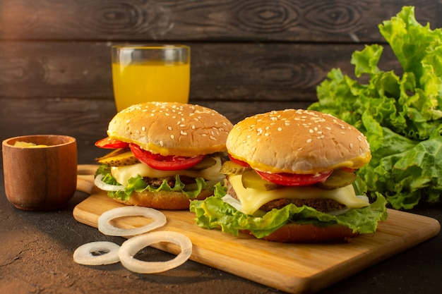 A front view chicken burger with cheese juice and green salad on the wooden desk and sandwich fast-food meal