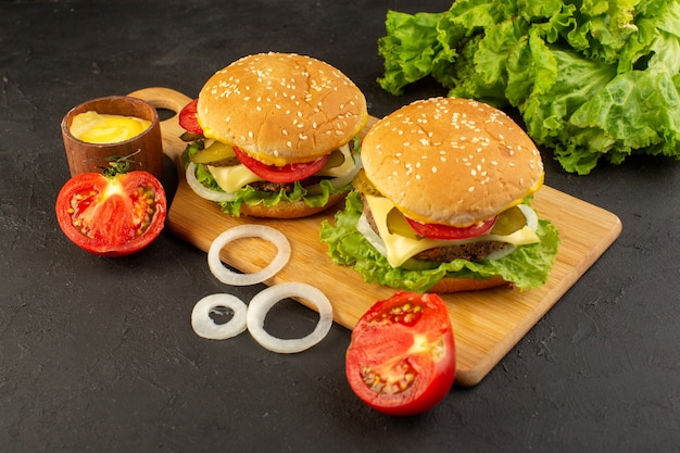 A front view chicken burger with cheese tomatoes and green salad on the wooden desk and sandwich fast-food meal