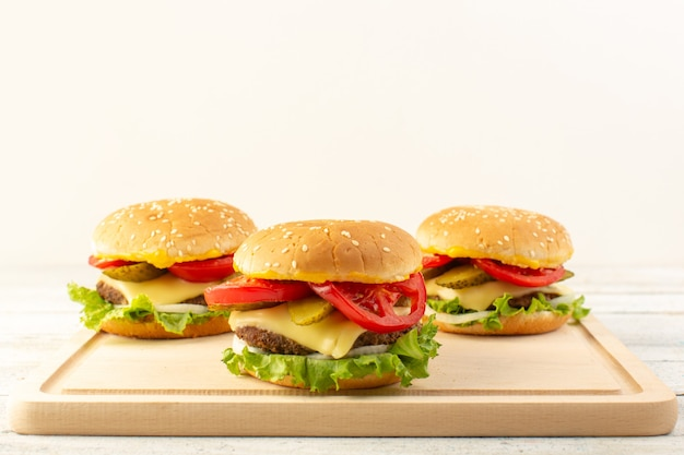 A front view chicken burgers with cheese and green salad on the wooden desk and sandwich fast-food meal
