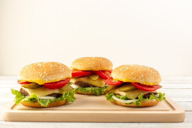 A front view chicken burgers with cheese tomato and green salad on the wooden desk and sandwich fast-food meal