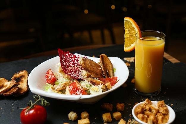 Салат цезарь с курицей, вид спереди на тарелке с апельсиновым соком и гренками на столе