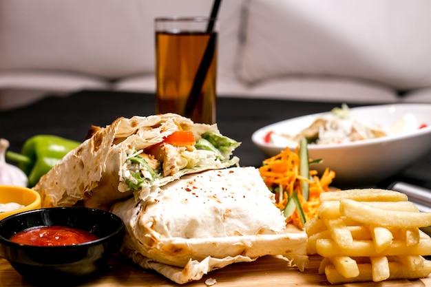Вид спереди куриного донера в лаваше с кетчупом, картофелем фри и овощным салатом на доске