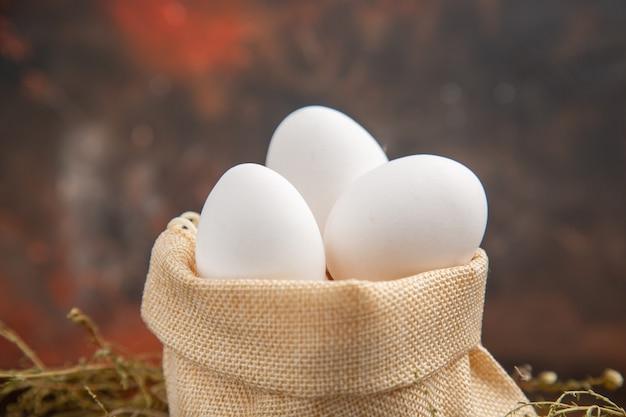Uova di gallina vista frontale all'interno della borsa sulla superficie scura