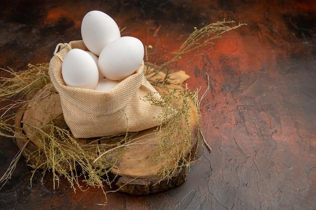 Куриные яйца, вид спереди, внутри сумки на темной поверхности