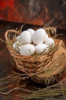 Uova di gallina vista frontale all'interno del cesto sulla superficie scura