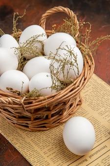 暗い表面のバスケット内の正面図鶏卵