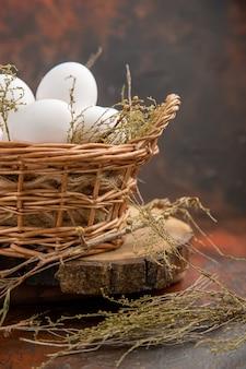 어두운 표면에 바구니 안에 전면보기 닭고기 달걀