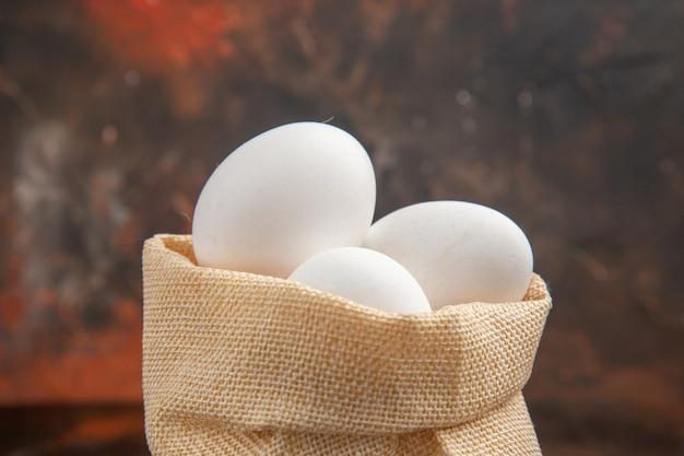 Uova di gallina vista frontale all'interno di una piccola borsa su superficie scura dark