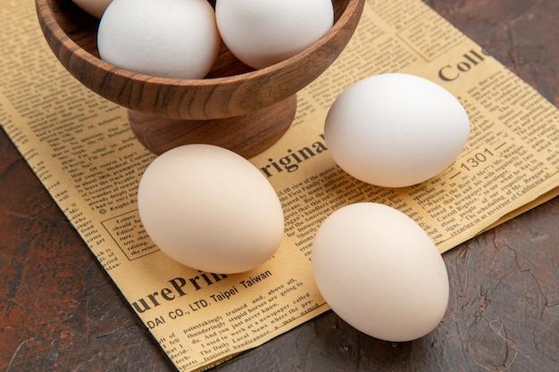 Uova di gallina vista frontale all'interno del piatto su superficie scura