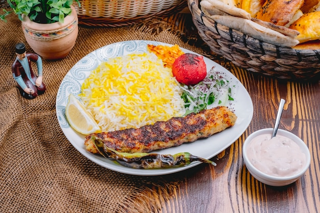 Front view chicken lula kebab with rice grilled vegetables and onions
