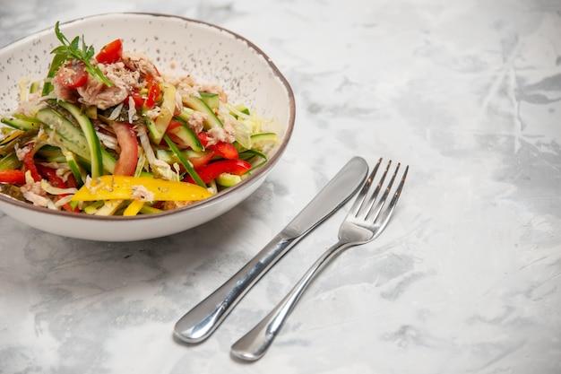 Vista frontale dell'insalata di pollo con verdure e posate su una superficie bianca macchiata