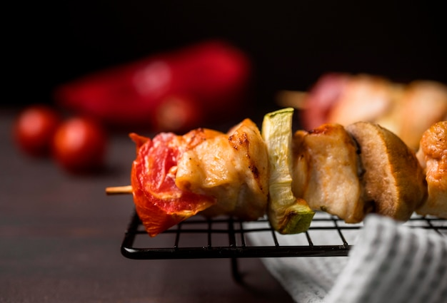 Front view chicken skewer on tray with red pepper