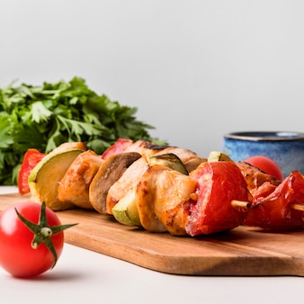 Front view chicken skewers on cutting board with tomato