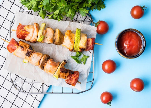 Front view chicken skewers on parchment paper with cherry tomatoes and sauce