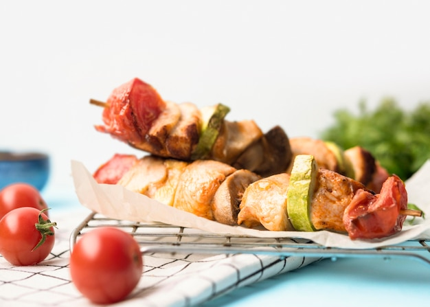 Front view chicken skewers on parchment paper with tomatoes
