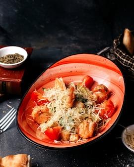 暗い床にトマトとチーズと共に鶏のスライスの正面図