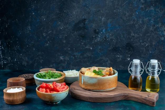 正面図ジャガイモと塩コショウの新鮮な野菜と紺色の机の上の油とチキンスープスープ肉料理夕食の食事