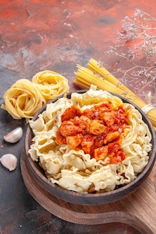 Pollo di vista frontale con piatto di pasta della pasta sulla pasta del piatto di pasta di superficie scura scuro