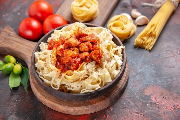 Pollo di vista frontale con il piatto di pasta della pasta sulla farina della pasta della pasta di superficie scura scuro