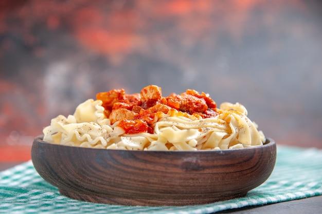 暗い表面色の食事パスタ皿に生地パスタ皿と正面図の鶏肉