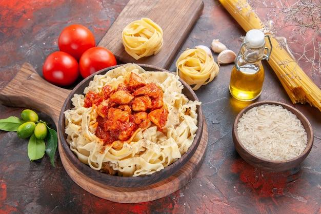 正面図チキンとトマトの生地パスタ料理、暗い表面のパスタ生地ミール