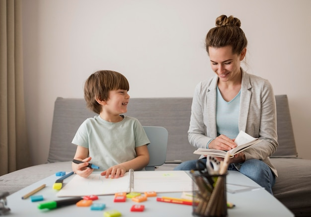 Front view of child being tutored at home by woman