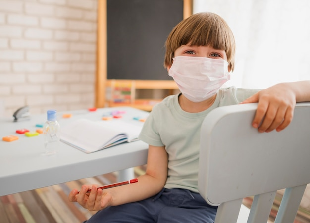 Front view of child being tutored at home while wearing medical mask