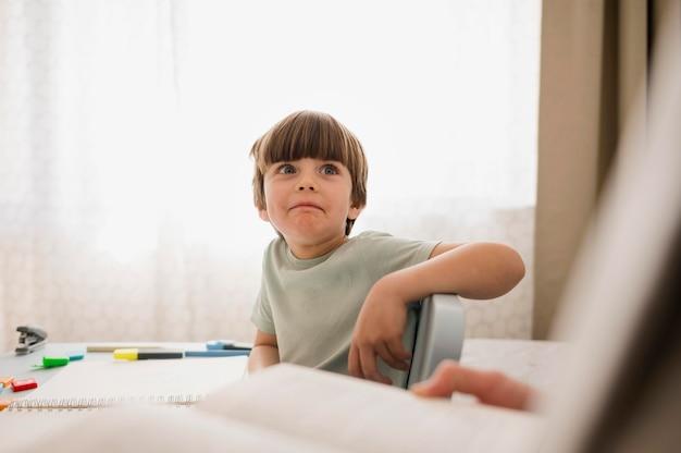 Vista frontale del bambino che è istruito a casa