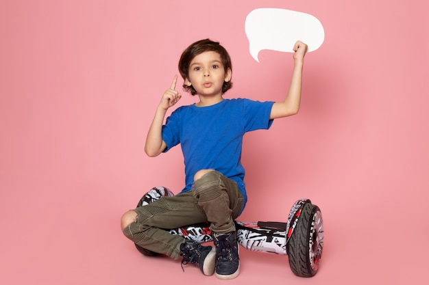 A front view child boy in blue t-shirt holding white sign sitting on the segway on the pink space