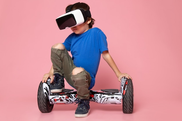 A front view child boy in blue t-shirt and khaki trousers riding segway on the pink floor