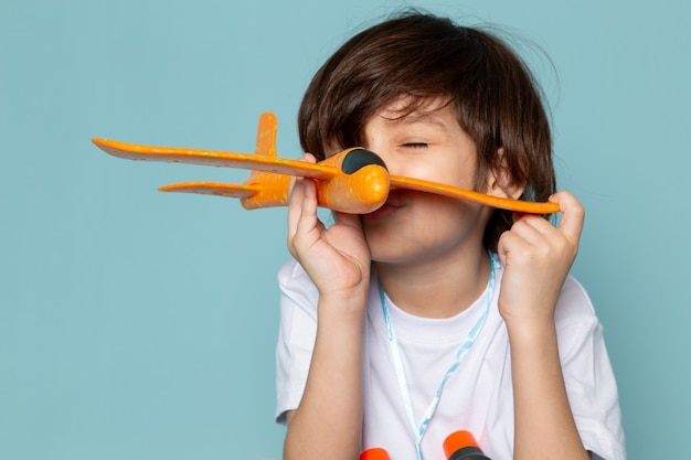 Front view child boy cute adorable playing with toy orange plane on the blue desk