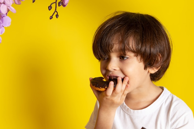 A front view child boy eating donuts with chocolate on the yellow space